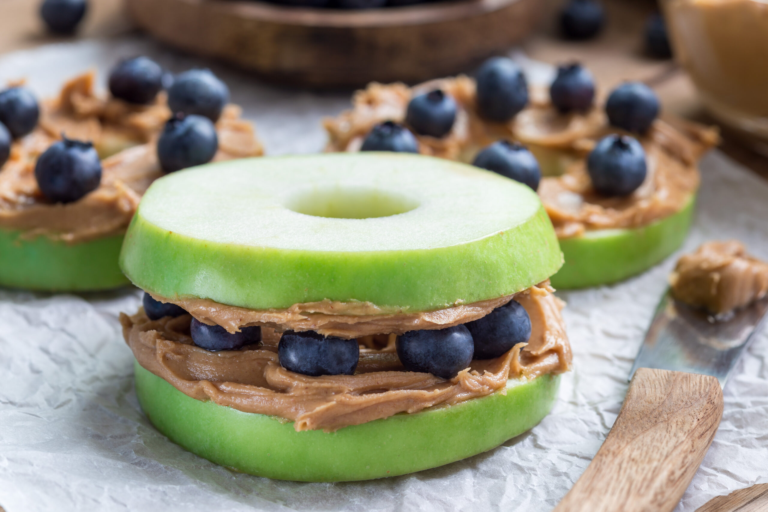 """peanut free snack """"sandwhich"""" made with apple, blueberries, and almond butter."""