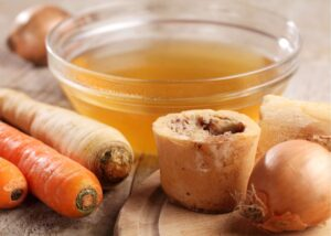 Carrots and a cup of bone broth which is a good food for arthritis and sore muscles.