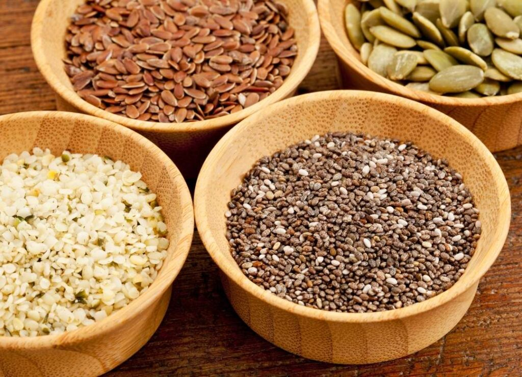 Bowls of hemp, chia, flax, and protein seeds which may be high-protein snacks.